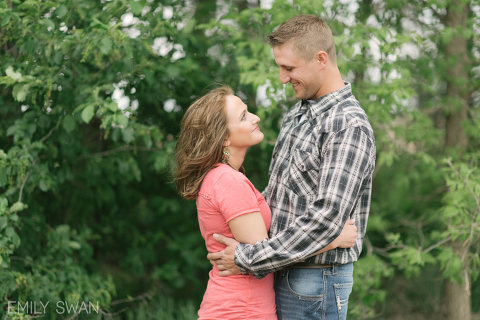 Larchwood Iowa summer engagement couple gazing lovingly at one another