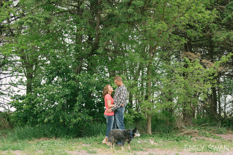 Larchwood Iowa couple stand in green trees with pets dog and cat Midwest engagement photography