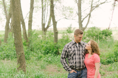 Cute couple on Iowa farm green with trees Midwest engagement photographer