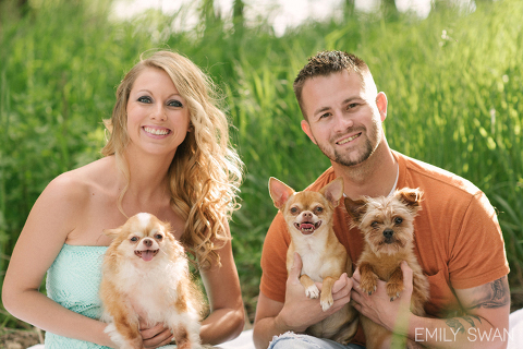 Couple smiles holding their 3 dogs summer Sioux Falls engagement photography