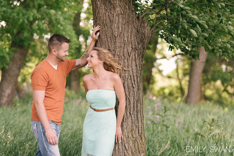 Couple smiling at each other posed against tree outdoor summer Sioux Falls engagement photographer