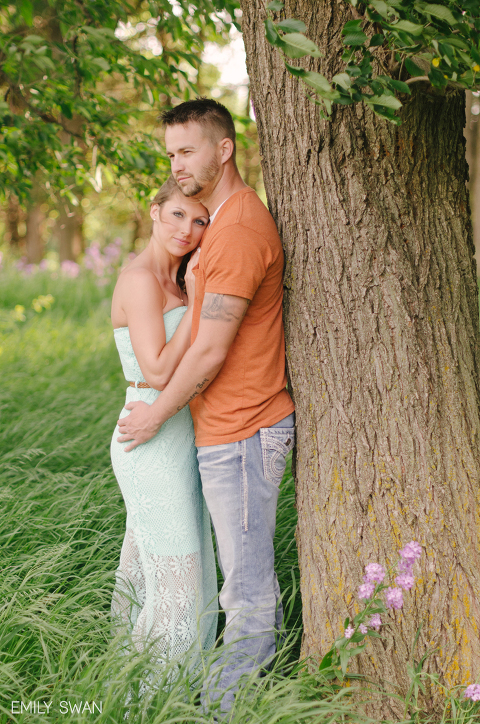 Romantic couple embracing by tree purple flowers summer Sioux Falls South Dakota engagement session