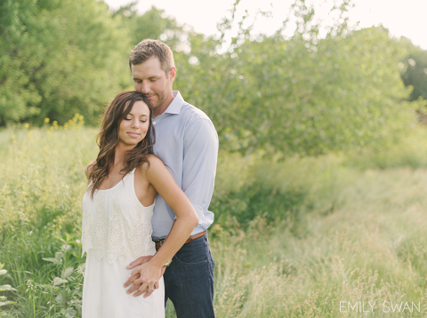 Romantic minimalist sunset prairie engagement couple embracing in tall grass