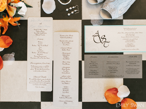 Wedding stationery suite on black and white checkered floor and orange flowers