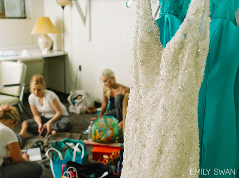 Beaded ivory wedding gown and teal bridesmaids dresses hanging in Sioux Falls Orpheum Theatre green room with girls in background