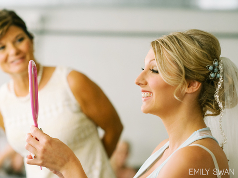 Bride looks at herself in mirror after getting her hair and makeup done with mom looking on and smiling