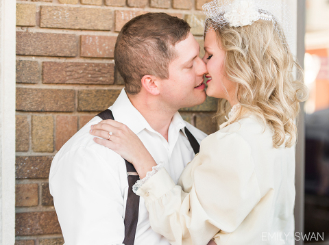 Kissing couple downtown Sioux Falls vintage themed engagement session