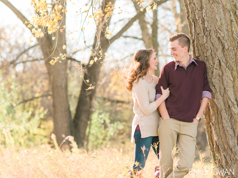 Autumn Sioux Falls engagement photographer cute couple in sweaters standing against tree Emily Swan photography