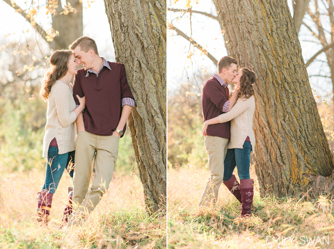 Sioux Falls engagement photographer couple standing with fall foliage kissing by Emily Swan Photography