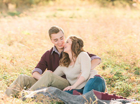 Candid engagement photographer Sioux Falls couple laughing laying on grass with fall colors Emily Swan
