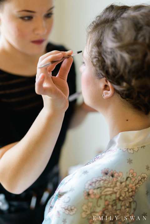 Midwest bride in robe having makeup done