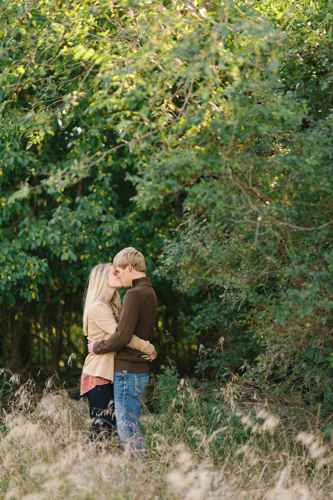 Couple standing in trees kissing Sioux Falls engagement picture