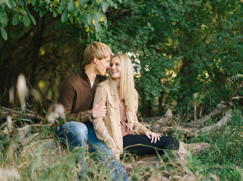 Couple sitting on log smiling at each other Sioux Falls engagement picture