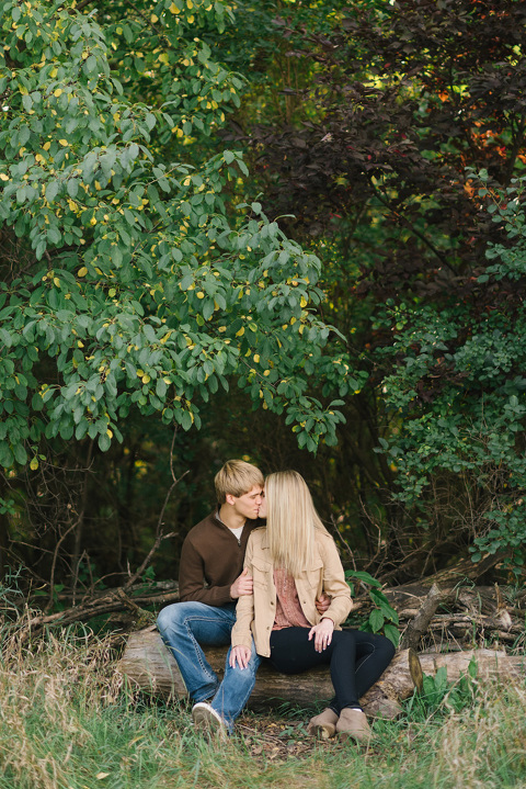 Sioux Falls engagement picture couple sitting on log in wilderness