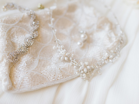 Wedding details of pearl jewelry and vintage ivory clutch