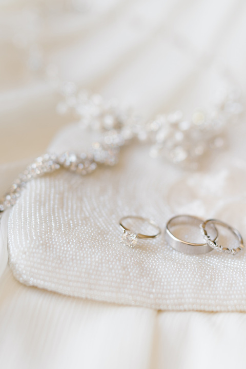 Classic wedding details solitaire diamond ring and ivory clutch