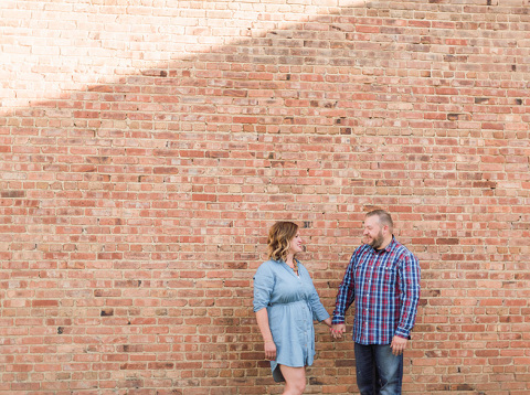Engaged couple holding hands against brick wall