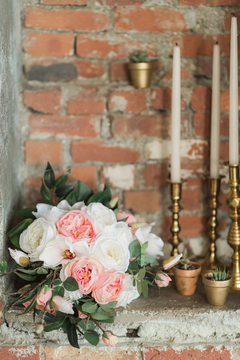 Brick wedding reception with gold accents and pink flowers