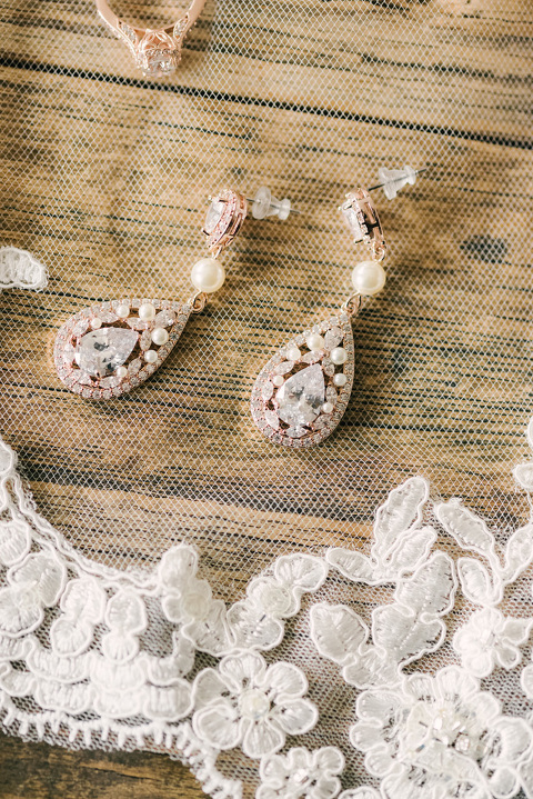 Wedding details rose gold diamond ring earrings and lace veil