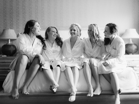 Bride with bridesmaids in custom silk robes laughing