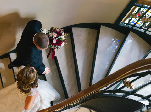 Bride and groom climbing marble staircase