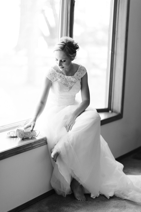 Black and white picture of bride sitting in windowsill