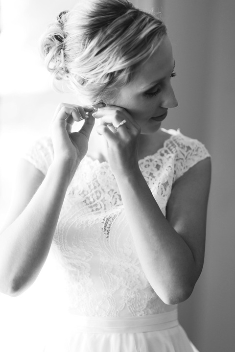 Picture of bride putting on jewelry black and white