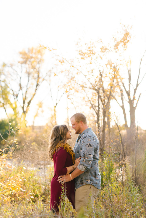 Couple standing in trees by river South Dakota engagement