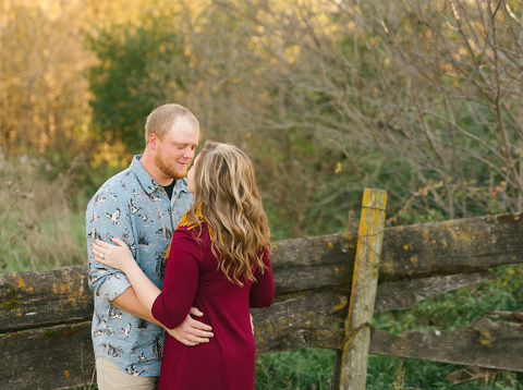 Sweet picture of engaged couple by old rustic fence