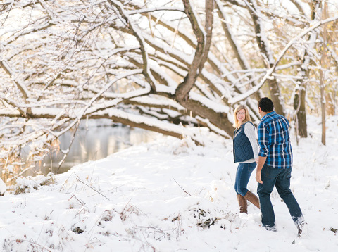 Engagement picture couple walking through snow