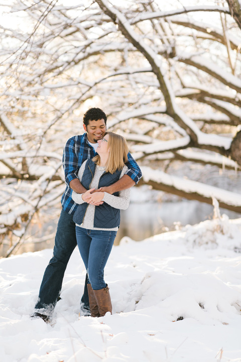 Cute snowy winter engagement picture of couple laughing
