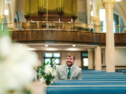 Groom smiling before ceremony floral pew decorations Midwest wedding