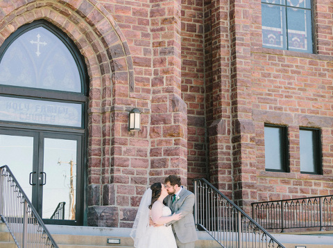 First look on church steps couple kissing South Dakota wedding photography