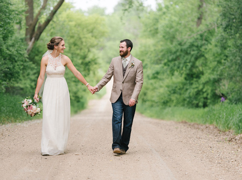 Bride and groom holding hands walking down deserted country gravel road South Dakota wedding photography