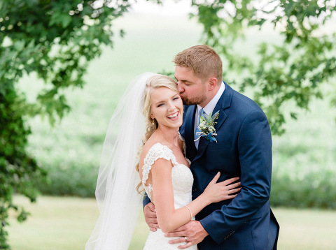 Joyful bride with long, romantic veil loving outdoor portrait mn wedding