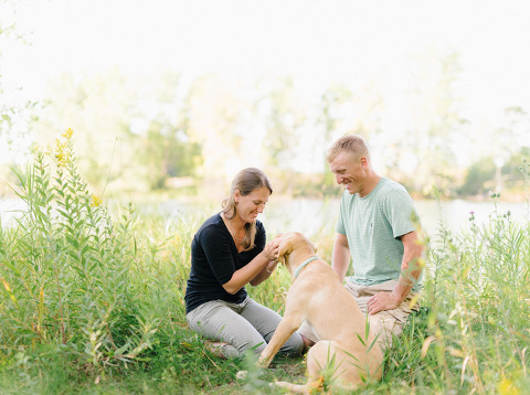 Summer lakeside engagement session with wildflowers couple smiling with dog in prairie grass