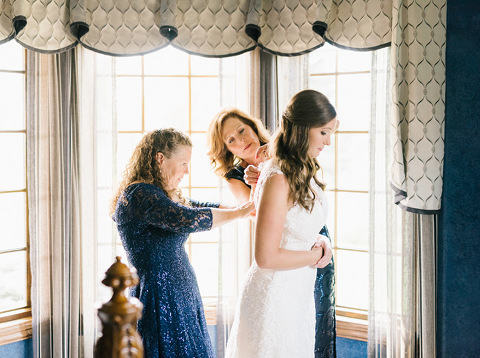 Mothers helper bride into her wedding gown natural light South Dakota wedding photographer