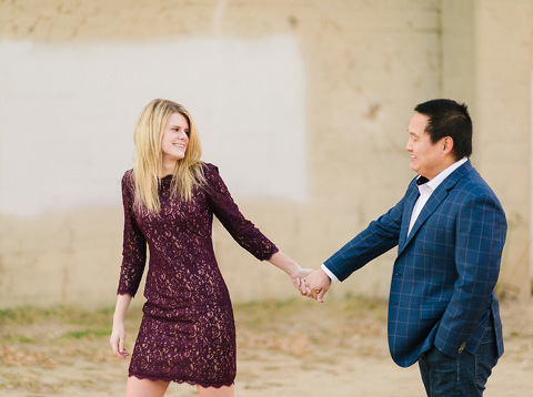 Engaged couple laughing leading hand in hand downtown Sioux Falls photography