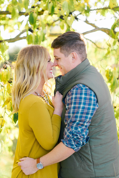 Sweet and natural engagement couple nose to nose with colorful autumn foliage