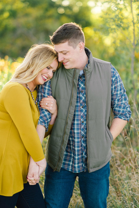 Natural candid genuine engagement posing couple laughing tall grass autumn colors