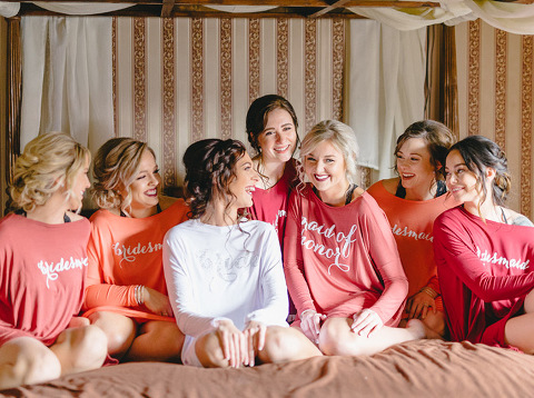 Bride with bridesmaids in custom getting ready tunics on bed laughing natural light