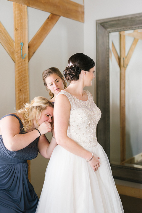 Bridesmaid helping bride get dressed Meadow Barn at Country Orchards