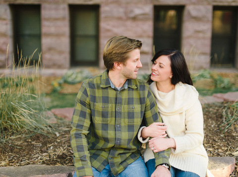 Couple sitting arm in arm downtown Sioux Falls engagement photography