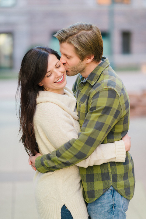 Winter downtown Sioux Falls engagement photography couple kissing brick building