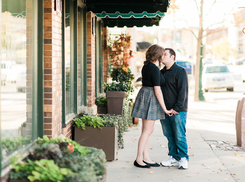 Couple kissing on downtown Sioux Falls city sidewalk engagement