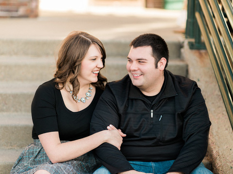 Engaged couple sitting on stairs and laughing downtown 8th and Railroad Sioux Falls