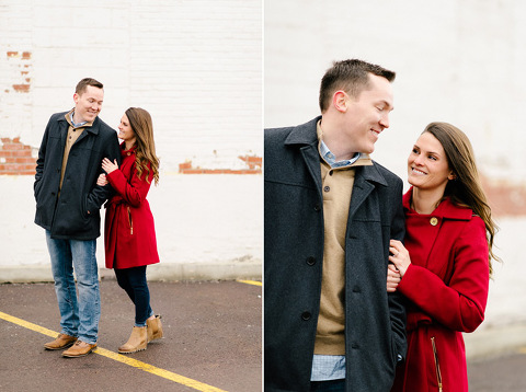 Couple in winter coats downtown engagement white brick building