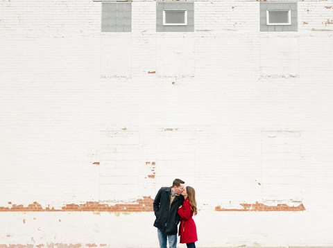 Couple kissing white brick building bright and airy Emily Swan Photography