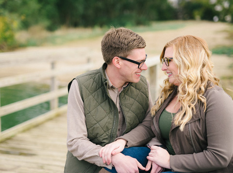 Couple smiling fall engagement session on South Dakota lake dock