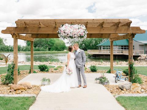 Bride and groom kissing wedding backdrop flower installation pond JP Denmark photography